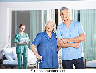 Confident Male Caretaker And Disabled Senior Woman