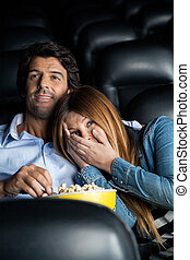 Scared Woman Leaning On Man In Cinema Theater