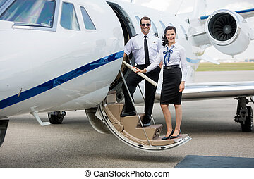 Airhostess And Pilot Standing On Private Jet's Ladder - Full...