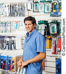 Man Standing In Hardware Store - Portrait of smiling young...