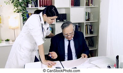 Doctors at work in office - Female doctor talking with...