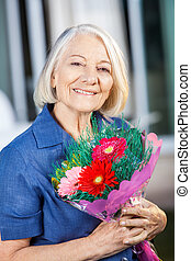 Happy Senior Woman Holding Bouquet At Nursing Home