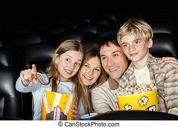 Happy Family Watching Movie In Theater - Happy girl showing...