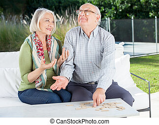 Happy Senior Couple Playing Dominoes At Nursing Home Porch
