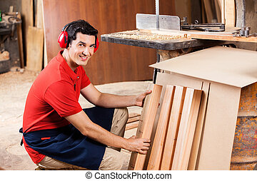 Carpenter Arranging Wooden Planks In Workshop - Portrait of...