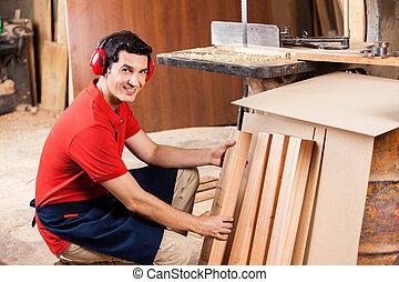 Carpenter Arranging Wooden Planks In Workshop - Portrait of...
