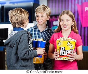 Girl Holding Popcorn While Brothers Talking At Cinema