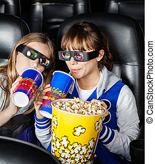 Happy Sisters Having Snacks In 3D Movie Theater - Portrait...