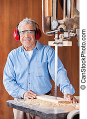 Happy Carpenter Cutting Wood With Bandsaw - Portrait of...