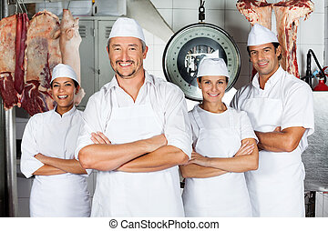 Male Butcher With Confident Team - Portrait of mature male...