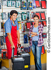 Customer And Salesman With Tool Cases In Store - Portrait of...