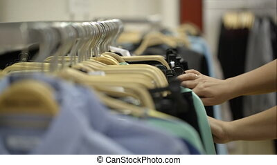 Woman looking over clothes in the store - Close-up shot of a...