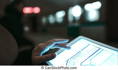 Woman looking at underground map using touch pad