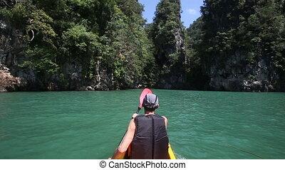 man rowing kayak in the canyon - elderly man rowing a kayak...