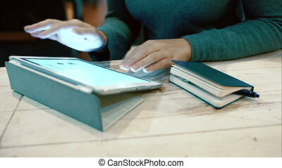 Woman working with pad and taking notes in notebook -...