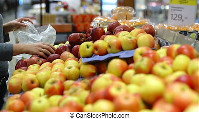 Woman in the supermarket putting apples in plastic bag -...