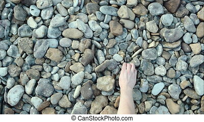 Male hand taking and throwing pebble stones - Close-up top...