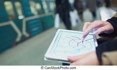 Woman searching station on underground map using touch pad -...