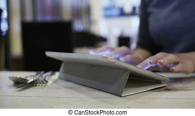 Woman in cafe using tablet PC to send a message
