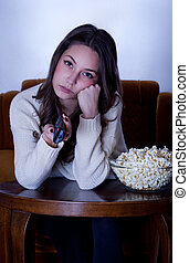 TV marathon - Beautiful young brunette woman watching TV in...