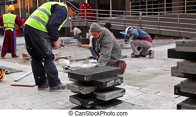 Pavers at work - Workers stack paving slabs on city streets