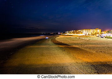View of buildings along the beach at night in Folly Beach,...
