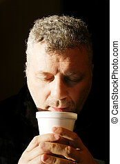 Coffee from Styrofoam Cup - A man drinking coffee from a...