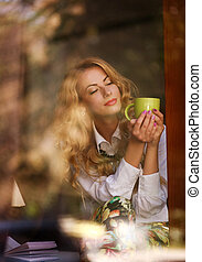 Dreamy woman with a cup of coffee in cafe, enjoying the...