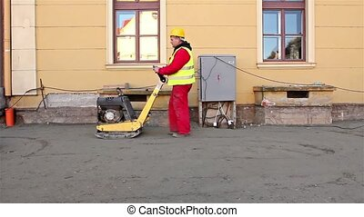 Soil Compacting - Vibrating machine is compacting soil at...