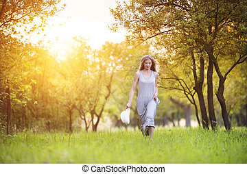 Beautiful woman outside in a park. - Attractive young woman...