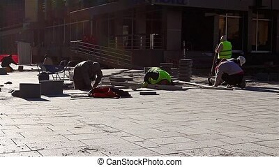 Paver at work - Workers stack paving slabs on city streets