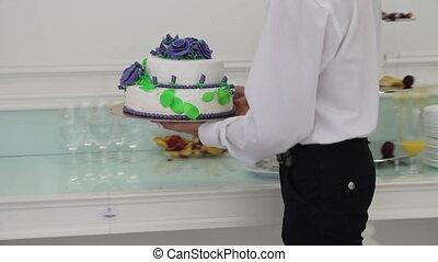 Wedding cake - waiter brings the wedding cake and newlyweds...