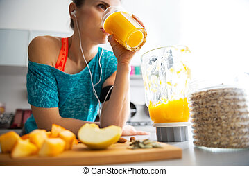 Close-up on fitness young woman drinking pumpkin smoothie in...