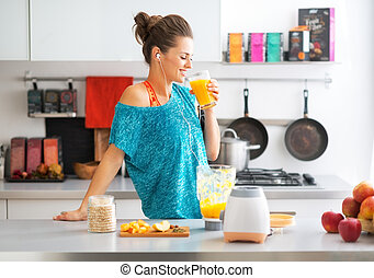 Happy fitness young woman drinking pumpkin smoothie in...