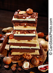 stack of various chocolate bars with nuts,raisins and coffee...