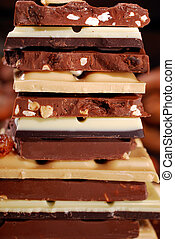 stack of various chocolate bars with nuts -closeup
