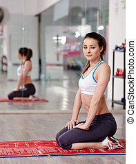 Fitness girl resting on a yoga mat in a gym