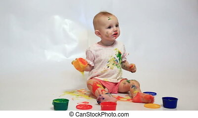 little girl soiled by paints sits on a white background
