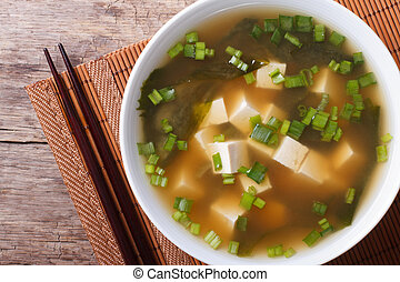 classic miso soup in a white bowl close-up horizontal top...