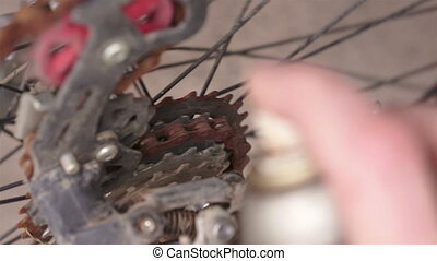 Lubricating Rusty Chain Sprocket - A close up shot of a...