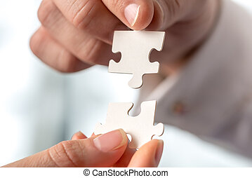 Two businesspeople fitting together puzzle pieces - Two...