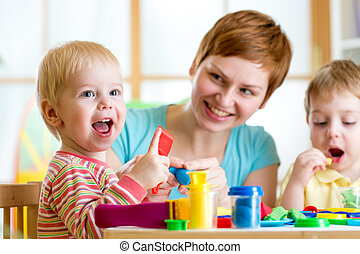 woman playing and teaching with kids - woman teaches kids...