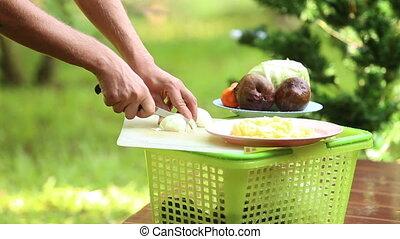 cooking ukrainian national soup borsch - man hands cut onion...