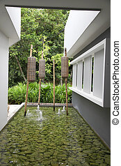 Zen water garden with wicker lanterns and pebbles