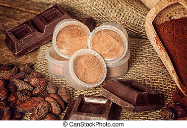 Capsules of chocolate with cocoa powder, cocoa beans and...
