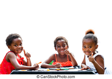 Three African girls doing thumbs up at table. - Portrait of...