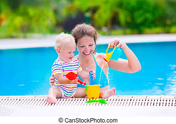 Mother and baby in swiming pool - Happy family, young active...