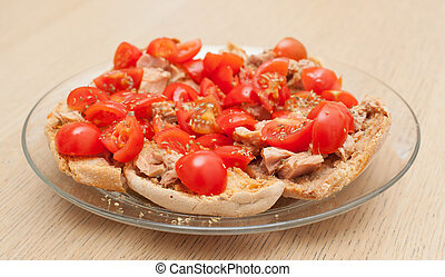 Dried bread called freselle with tuna and tomatoes on wooden...