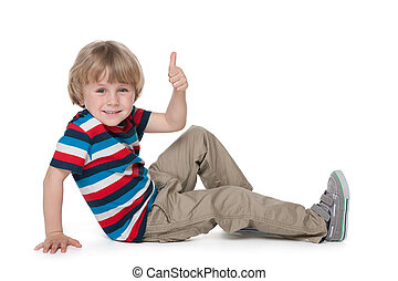 Little blond boy sits on the floor