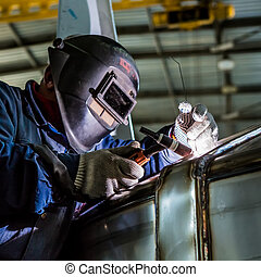 Man welding with reflection of sparks on visor Hard job...